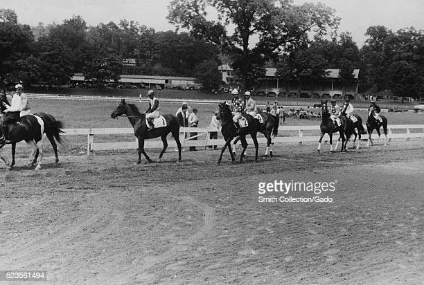 Photograph of race horses being paraded to the starting gate prior to the start of the race, people are gathered in the infield, cars can be seen...