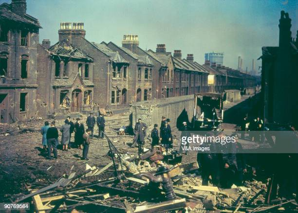 Photograph of residents inspecting bomb damage to houses in London during the blitz Battersea power station can be seen in the background
