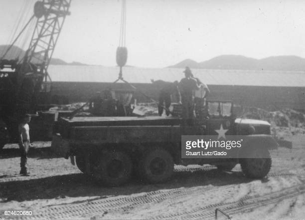 A photograph of several United States Army serviceman unloading building supplies from an M35 military truck other building materials are located...