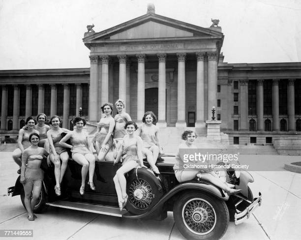 Photograph of several young women in two-piece beachwear flanking a Packard in front of the Oklahoma State Capitol building, Oklahoma City, Oklahoma,...