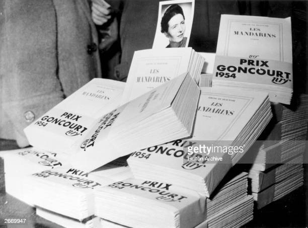 A photograph of Simone de Beauvoir French novelist and advocate of existentialism amongst copies of her book 'Les Mandarins' which received the Prix...