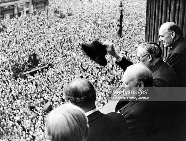 Photograph of Sir Winston Churchill British statesman who was the Prime Minister of the United Kingdom looking out over crowds celebrating the end of...
