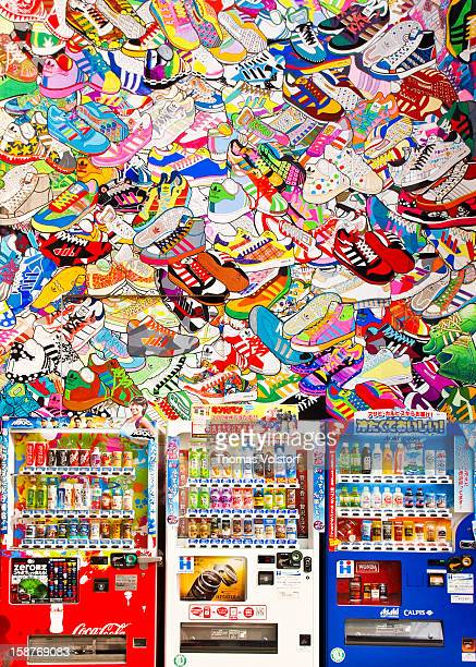 Photograph of soft-drink vending machines taken against the background of the colorful back wall of a shoe retail / brand store in Shinjuku, Japan....