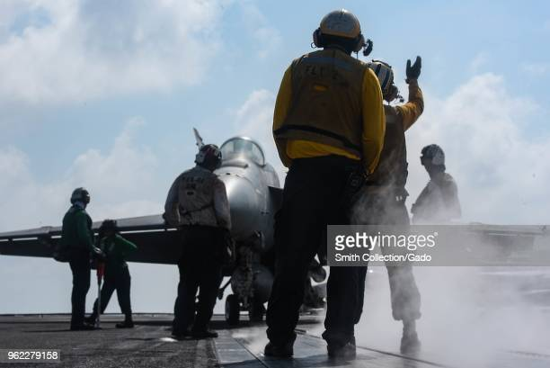 Photograph of solders including 2nd Class Duane Hill and Airman Kodie Rippee on the flight deck of the Nimitz-class aircraft carrier USS Harry S...