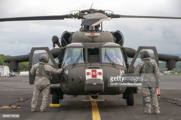 Photograph of soldiers from the Hawaii Army National Guard preparing an HH60 Black Hawk utility helicopter for flight as part of rescue operations...