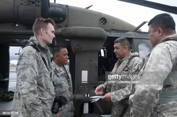 Photograph of soldiers involved in Task Force Hawaii consulting with one another prior to an aerial survey of areas affected by recent volcanic...