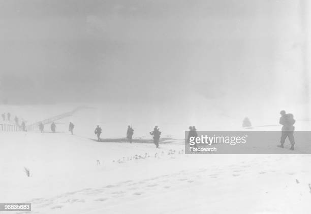 A Photograph of Soldiers of an Infantry Division moving into the Mist toward their Objective over a Snow Covered Field near Krinkelter Belgium...