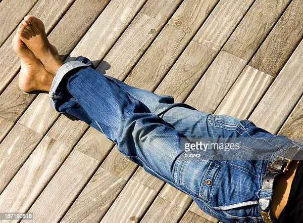 A photograph of some legs in jeans with ankles crossed