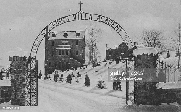 A photograph of St John's Villa Academy taken from outside of the gate the gate is made up of stones walls and pillars with fencing and an archway...