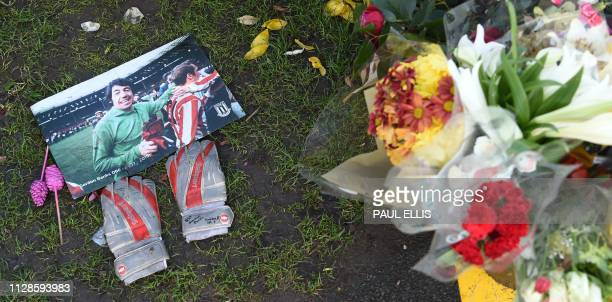 A photograph of Stoke City and England's former goalkeeper Gordon Banks is pictured next to a pair of goalkeeper's gloves amid floral tributes to...