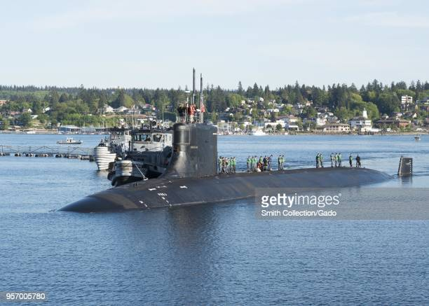 Photograph of submariners standing on top of the Seawolfclass fastattack submarine USS Connecticut in the water at Naval Base KitsapBremerton...