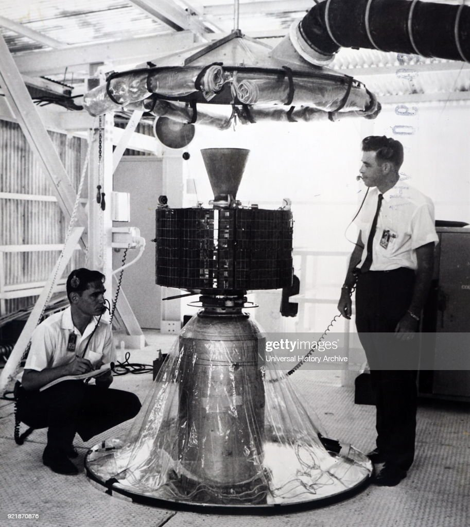 Photograph of Syncom 2 - Technicians check the mating of the Syncom communications satellite atop the third stage of the Delta launch vehicle at Cape Canaveral, Florida. Dated 20th century.