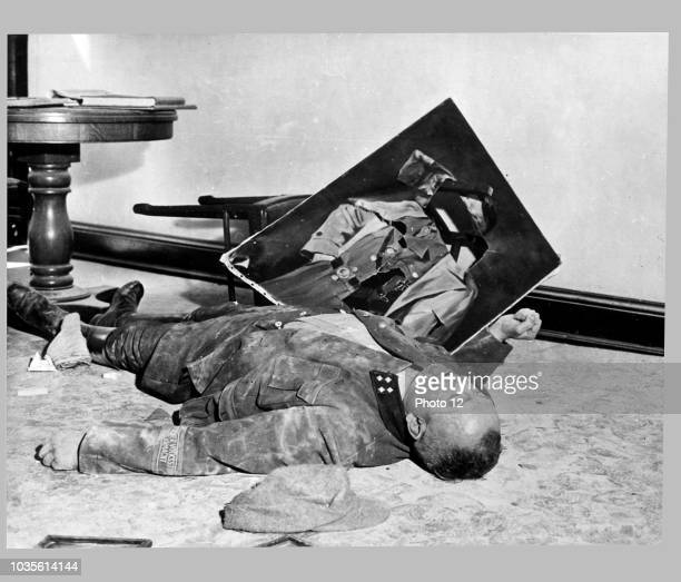 Photograph of the body of Walter Doenicke battalion leader of a German national militia lies next to a torn portrait of Hitler In Leipzig Dated 1945