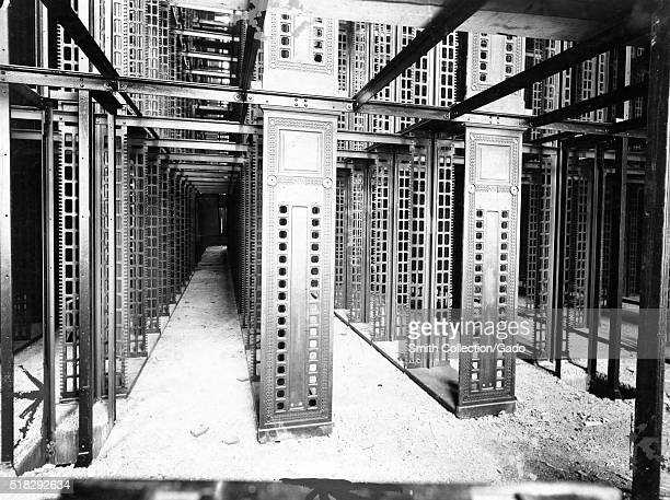A photograph of the construction of the stacks at the main branch of the New York Public Library the image shows long lines of framework for metal...