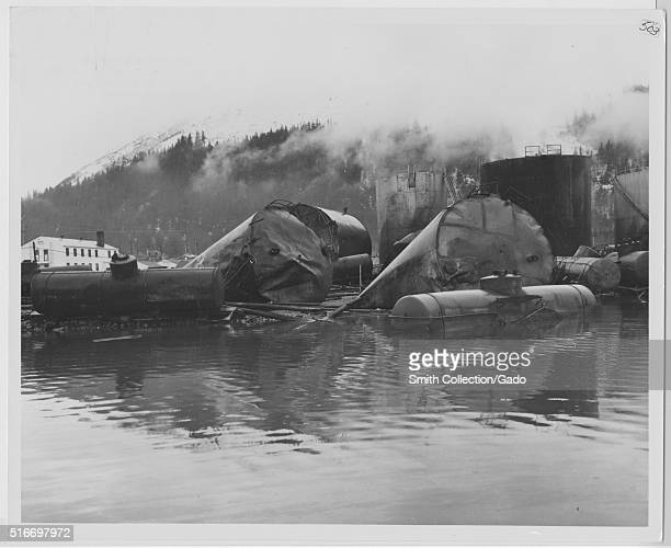 A photograph of the damage done to the Alaska Railroad Yard and Texaco bulk plant after the 1964 Alaska earthquake large tanks and rail cars can be...