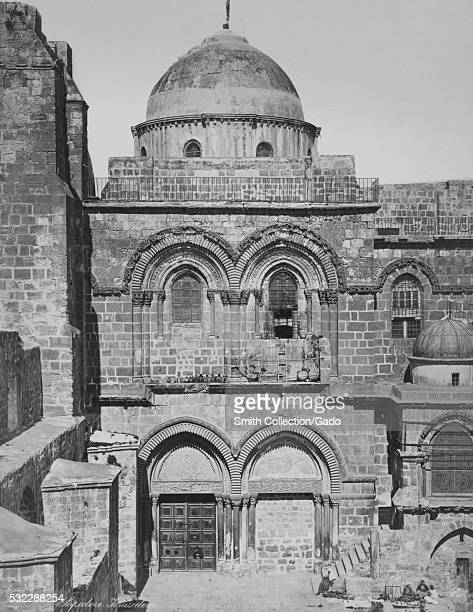 Photograph of the entrance to the Church of the Holy Sepulchre, the building is a stone work structure that has doorways and windows accented by...