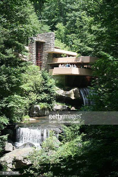 A photograph of the exterior of the home known as Fallingwater a group of tourists stand on a balcony that overlooks the waterfalls which run under...