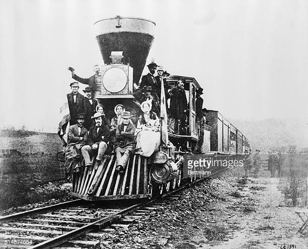 Photograph of the first locomotive to cross the Allegheny Mountains Passengers ride the cowcatcher