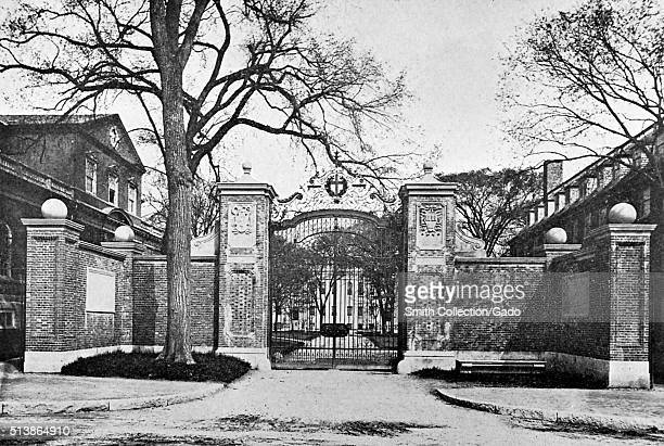 A photograph of the Harvard Gate it is now called the Johnson Gate the gate is one of several entrances to Harvard Yard the gate consists of a...