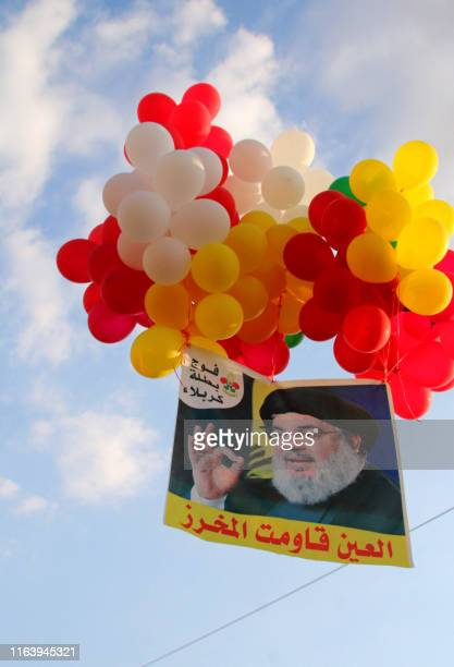 A photograph of the Lebanese Shiite Hezbollah movement leader Hasan Nasrallah is attached to colourful ballons during a gathering event organised by...