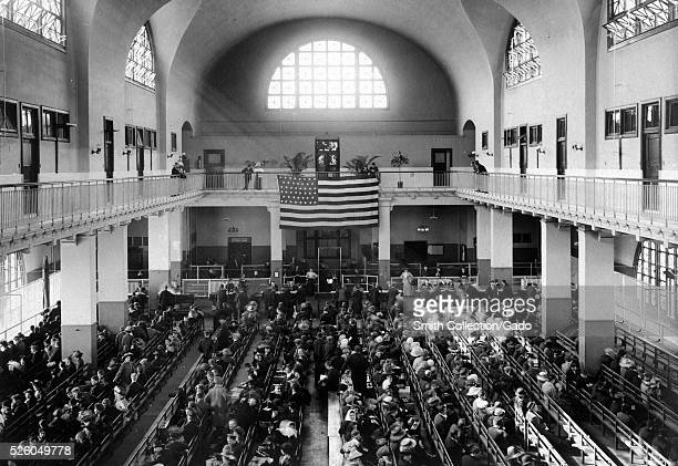 Photograph of the main hall of the United Station immigration inspection station on Ellis Island, immigrants line the benches of the main hall while...