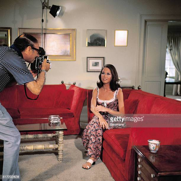 Photograph of the television star Mary Tyler Moore star of the Mary Tyler Moore Show being photographed Moore is wearing a sleeveless flowered dress...