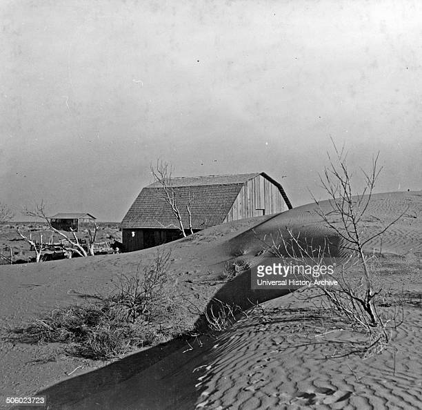 Photograph of the winds of a dust bowl that have piled up large drifts of soil against this farmer's barn near Liberal, Kansas. Dated 1936 Photo by: