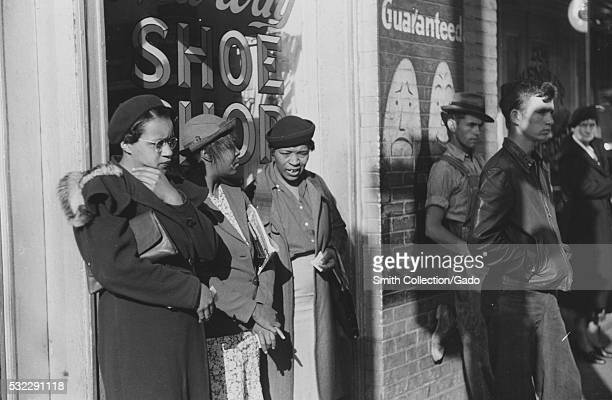 A photograph of three African American women who were identified as domestic helpers waiting for a street car all three women are wearing coats and...