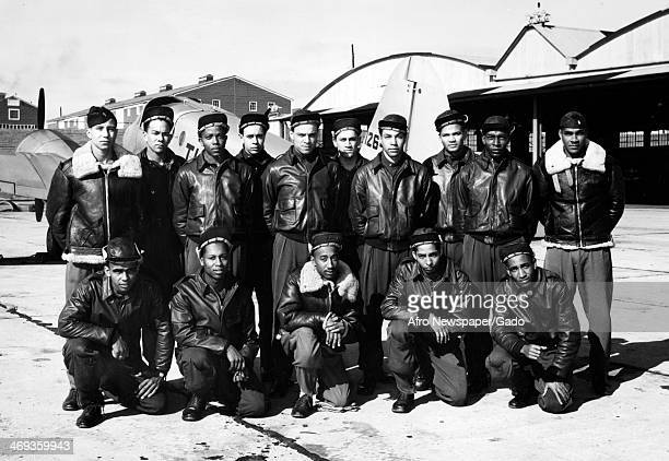 Photograph of Tuskegee Airmen during World War II wearing leather bomber jackets and standing with an airplane Tuskegee Alabama 1944