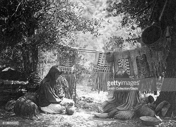 A photograph of two Apache women both women are seated and facing each other the woman on the left examines a piece of pottery at her feet while the...