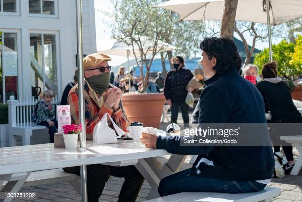 Photograph of two men, one wearing a bandana face mask, sitting at a table at a restaurant patio on a sunny day, Larkspur, California, February 13,...