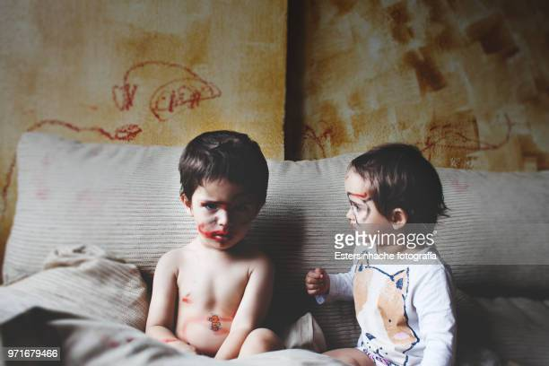photograph of two surprised twin brothers painting the living room walls - mischief stock photos and pictures