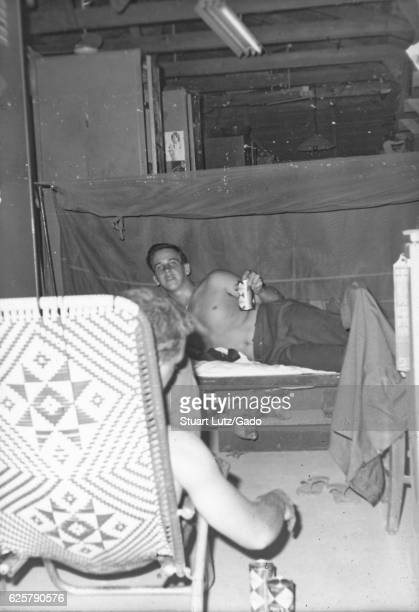 A photograph of two United States Army serviceman socializing in their barracks one soldier is lying in bed and holding a can of Coca Cola another...