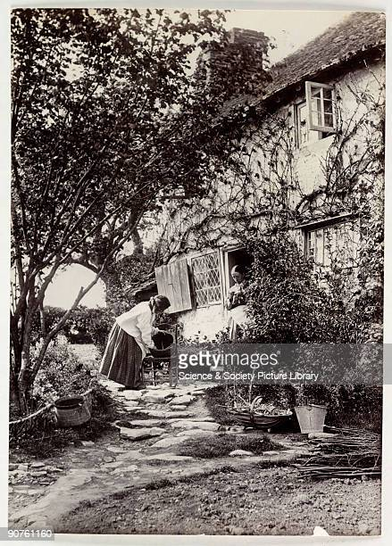 A photograph of two women in a garden taken by Colonel Joseph Gale about 1890 One woman stands in the doorway of the cottage sewing the other is busy...