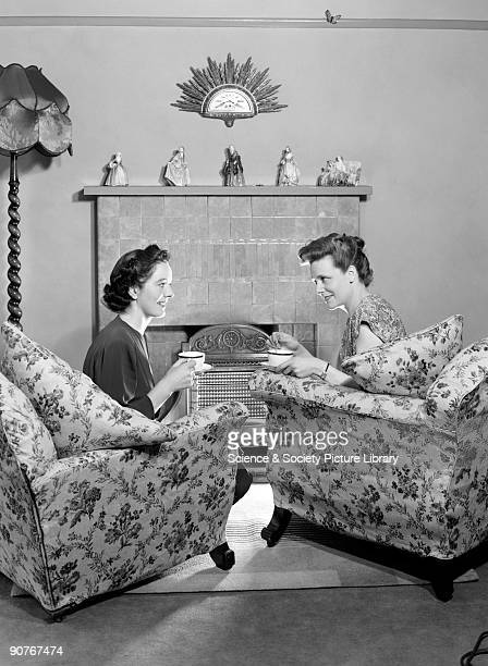 A photograph of two women sitting in armchairs talking and drinking tea This photograph was taken by Photographic Advertising Limited in 1948...