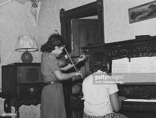 Photograph of two young girls playing instruments together, the girl on the left is standing and plays a violin, the girl on the right is seated and...