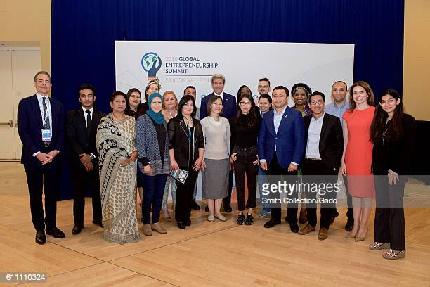 Photograph of US Secretary of State John Kerry Rick Stengel and Evan Ryan taking a group photograph with alumni of the State Department's Bureau of...