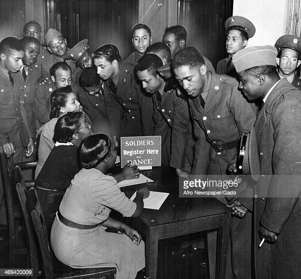 Photograph of USO hostesses signing registering soldiers for a dance, Japan, January 24, 1942.