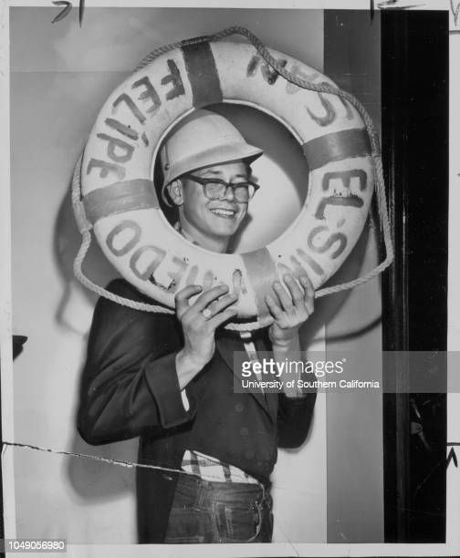 Photograph of Vern Watkins of the California Boys Republic displaying items for sale at the organization's 79th semiannual rummage sale at Pasadena...