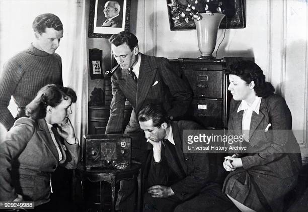 Photograph of Vichy French civilians listen to a radio broadcast by Admiral Jean Darlan French Admiral and political figure He was Admiral of the...