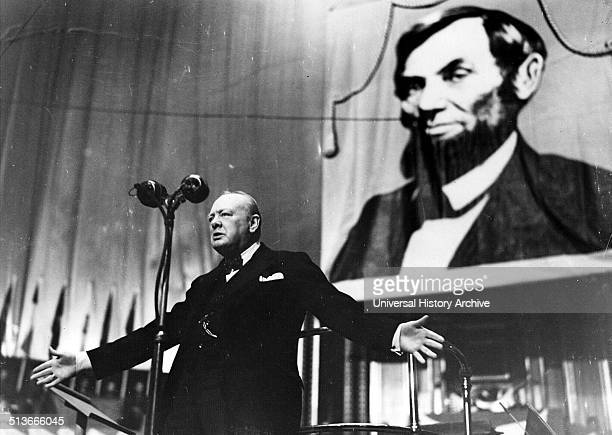 Photograph of Winston Churchill speaking at the Albert Hall in front of a large picture of Abraham Lincoln . Dated 1944