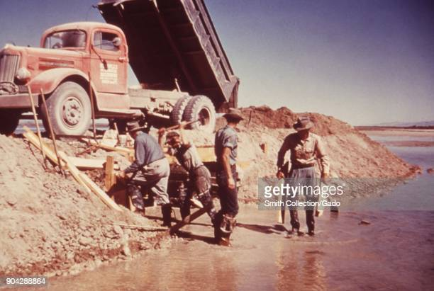 Photograph of workers with their feet in water next to an embankment and a dump truck constructing a dike and weir as part of the Wheeler Project in...