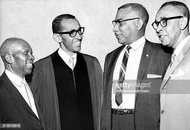A photograph of Wyatt Tee Walker who is the second from the left speaking with three other men who are local civic and church leaders after a speech...