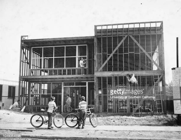 Photograph ofwo children with bicycles watching the construction of a youth center 5 October 1949 A sign at right reads 'Money Harold Harby City...