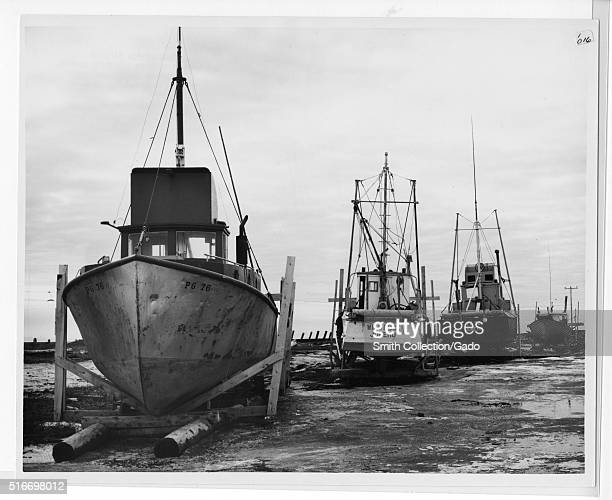 A photograph showing a line of boats that have been drydocked following the 1965 Alaska Earthquake the boats sit in an area covered in wet mud that...