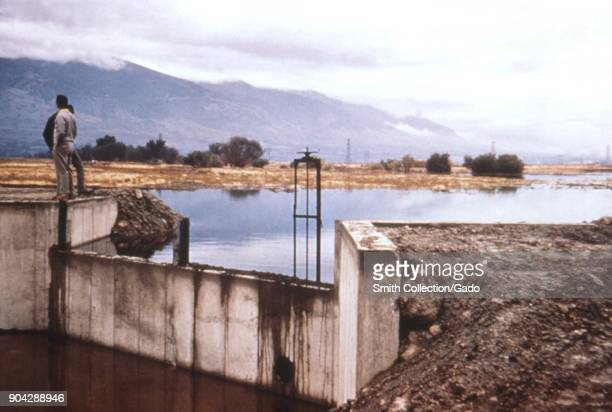 Photograph showing a view with a concrete floodgate at a water reservoir with two people standing beside it and a mountainous landscape in the...