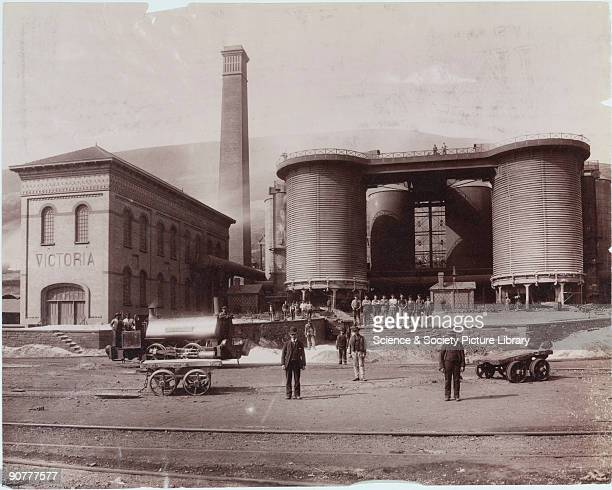 Photograph showing an industrial landscape with the workers of Victoria works in front of the Victoria blast furnaces a colliery steam engine and...