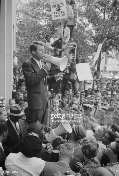 Photograph showing Attorney General Robert F Kennedy speaking to a crowd of African Americans and whites through a megaphone outside the Justice...