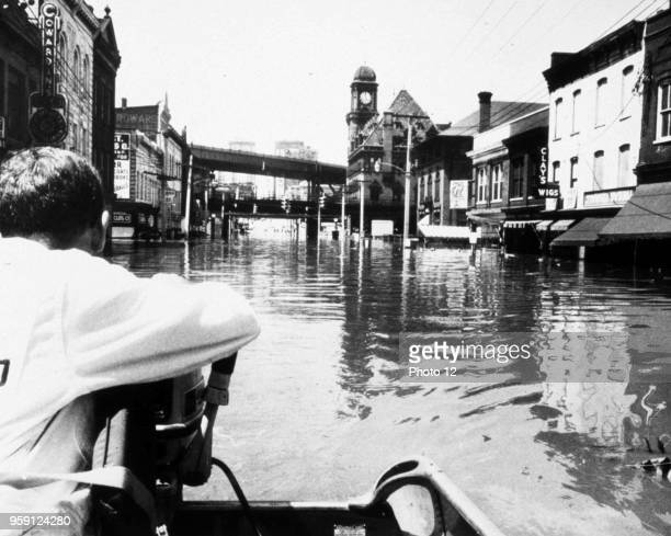 Photograph showing the remnants of Hurricane Camille which still packed a powerful punch Traveling through the business district by boat. Richmond,...