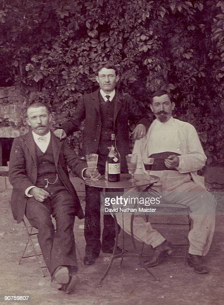 Photograph showing three gentleman sharing a bottle of Absinthe Pernod Fils Two of the glasses show the traditional band or 'cordon' at the base...